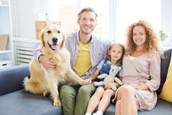 Happy and healthy family of mother, father, daughter and their cute pet sitting on sofa