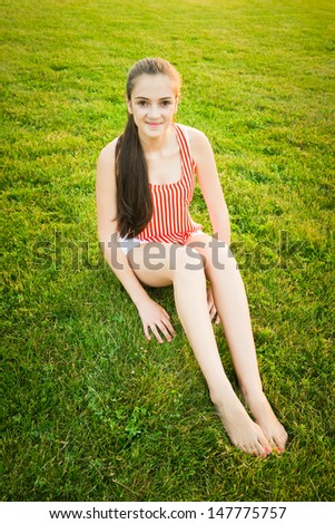Happy and healthy girl sitting in the park during dusk