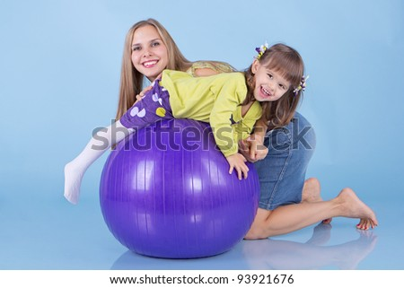 Happy and healthy little girl making gymnastic exercises with her mother indoors