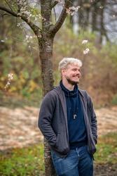 Happy and healthy man living with HIV leaning on a tree with blossoms in a park in Hamburg, Germany