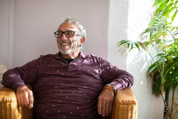 Happy and healthy senior man living with HIV sitting in a wicker chair looking away