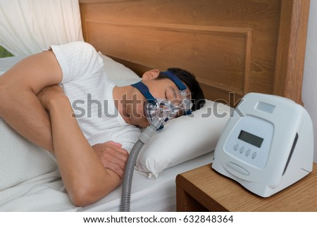 Happy and healthy senior man wearing Cpap mask sleeping smoothly all night long on his left side with cross arms without snoring, high angle view.Obstructive sleep apnea therapy.   Foto stock ©