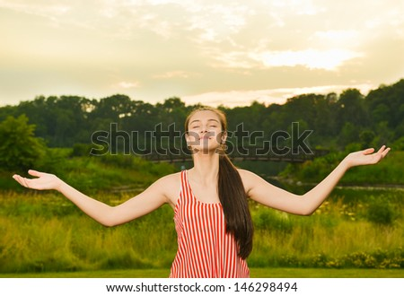 Happy and healthy woman meditating in one with nature at dusk