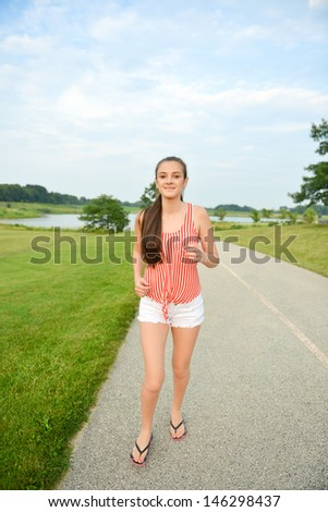 Happy and healthy woman walking/running in the park