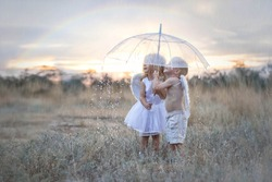 Happy and inspired angels boy and girl stand in the pouring rain hiding under an umbrella. A rainbow is visible in the sky. Thin streams of rain are barely visible on the whole background.