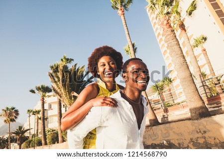 Happy and laugh couple in playful activity together outdoor in tropical place. smiles and joyful concept for black skin race diversity man and woman. Cheerful people in joy outside carrying on back #1214568790