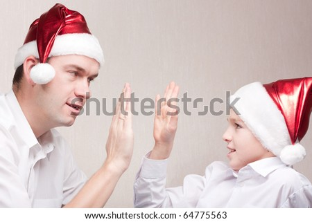 Happy and merry father and son in santa hat - stock photo