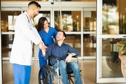 Happy and recovered patient sitting on a wheelchair and saying goodbye to his doctor while leaving the hospital