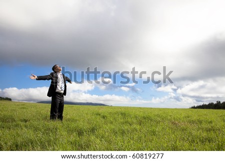 happy and Relaxation businessman standing on the green field enjoy sunlight