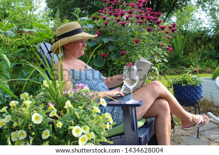 Happy and Relaxed Mature Woman 50 plus enjoying a glass of wine and reading a book in her beautiful garden
