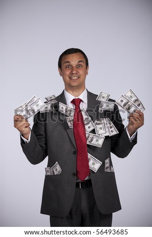 Happy and rich businessman showing all his money