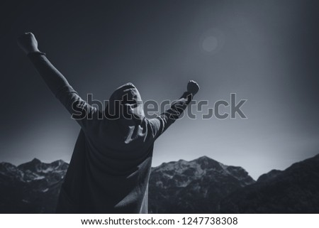 Happy and satisfied female traveler with hands raised in victorious V pose standing at the top of mountain and looking at the horizon