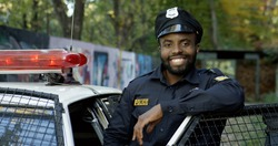 Happy and smiling African American police officer looking at camera