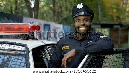 Happy and smiling African American police officer looking at camera Stock fotó ©