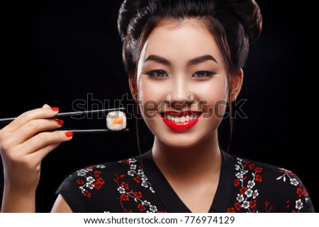 Happy and smiling Asian woman eating sushi and rolls on a black background.