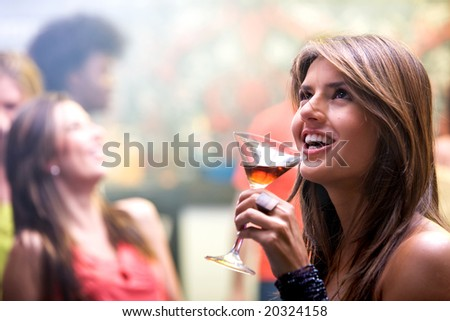 happy and smiling woman in a bar or a nightclub having a cocktail drink