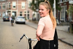 Happy and smiling young Dutch woman riding a bicycle through some streets in the Netherlands