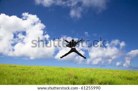 happy and successful Businessman jumping on a green meadow