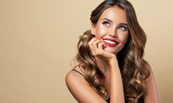 Happy and surprised girl  smiling  looking to the side presenting  your product . Beautiful curly hair woman amazed ,   with red nails manicure. Expressive facial expressions. Pin up