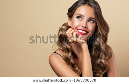 Happy and surprised girl  smiling  looking to the side presenting  your product . Beautiful curly hair woman amazed ,   with red nails manicure. Expressive facial expressions. Pin up Foto stock ©