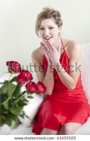 Happy and surprised woman receiving red roses on Valentine's Day or Birthday or Wedding Anniversary