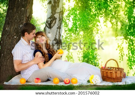 Happy and young pregnant couple hugging in nature enjoying summer park, outdoors, new life concept.