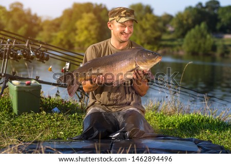 Happy angler with carp fishing trophy  #1462894496