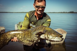 Happy angler with catfish fishing trophy