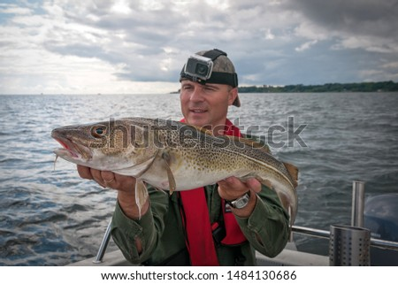 Happy angler with cod fishing trophy #1484130686