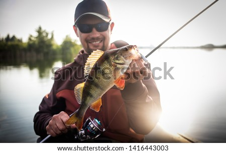 Happy angler with perch fishing trophy.	 #1416443003