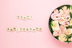 Happy anniversary lettering on the wooden squares with letters on the pink background and big round box with red flowers and roses.