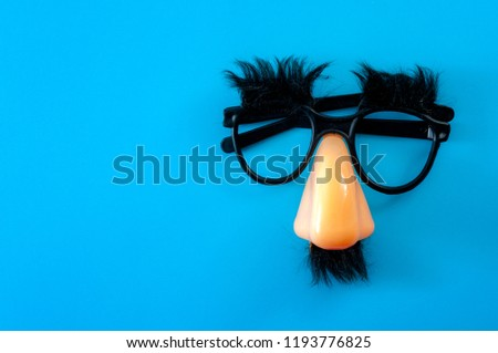 Happy april fool's day and funny pranks concept with a pair of comical glasses with bushy eyebrows and thick mustache isolated on blue background with copy space Сток-фото ©