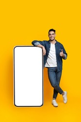 Happy arab guy leaning on huge smartphone with empty screen and showing thumb up, mockup, yellow studio background, full length shot, copy space, mobile application, advertisement concept