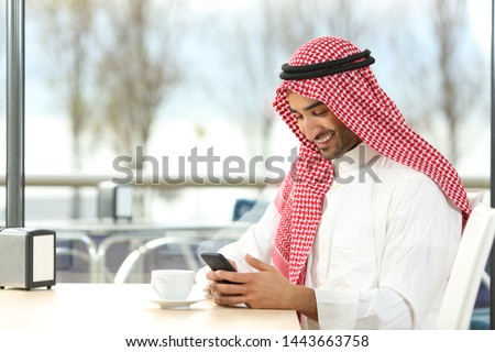 Happy arab man using a smart phone sitting in a coffee shop interior