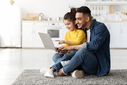 Happy Arab Man With His Little Daughter Using Laptop Together At Home, Middle Eastern Dad And Female Child Using Computer For Online Shopping Or Browsing Internet While Relaxing On Floor In Kitchen
