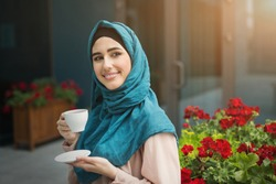 Happy arab woman in hijab drinking coffee in cafe outdoors, copy space