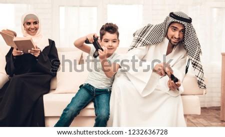Happy Arabian Family Playing on Console at Home. Family Sitting on Sofa. Man Using Digital Device. Smiling Boay at Home. Muslim Family. Smiling Boy. Young Arabian Woman. Woman in Black Dress.