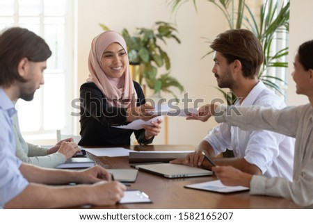 Happy arabian female team leader in hijab taking paper documents from colleagues, satisfied with colleagues working results. Diverse teammates submitting reports to smiling company boss at office.