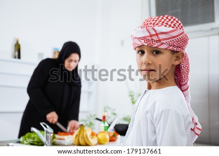 Happy Arabic child in the kitchen with his mother