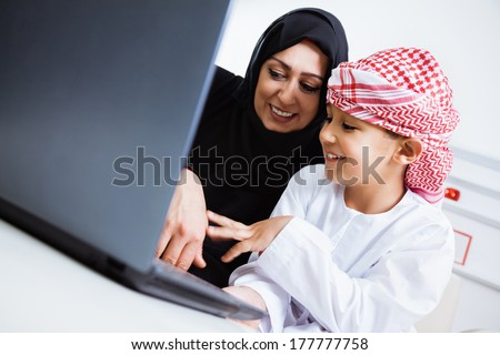 Happy Arabic mother and son together sitting on the couch and using laptop.