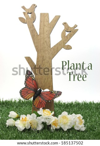 Happy Arbor Day, Plant a Tree greeting for last Friday in April, with wood tree, carved birds, butterfly and green grass on white background with sample text or copy space.