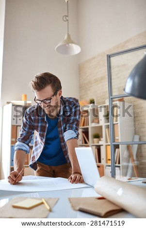 Happy architect in casualwear making sketch in office