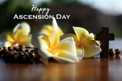 Happy Ascension Day concept with wooden rosary beads, Jesus Christ holy crucifix, Bali frangipani flowers and sun rays over the holy cross. Ascension day of Jesus Christ.