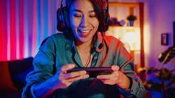 Happy asia girl gamer wear headphone competition play video game online with smartphone colorful neon lights in living room at home. Esport streaming game online, Home quarantine activity concept.