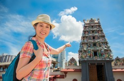 Happy Asia woman Travel in Singapore, Pointing Sri Mariamman Temple