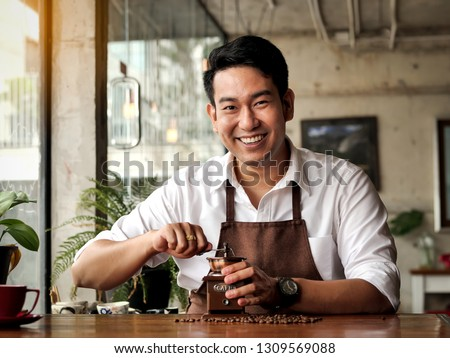 Happy Asian barista man grinding coffee beans on table, lifestle concept.