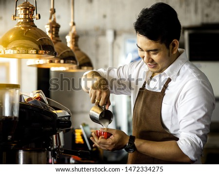 Happy Asian barista pouring milk into red coffee cup for latte art.
