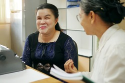 Happy Asian blind person woman with vintage braille typewriter or Brailler for people with vision disabilities, working and talking with senior colleague woman in office workplace.