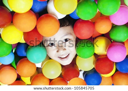 Happy asian boy playing with colorful balls, shot at playground