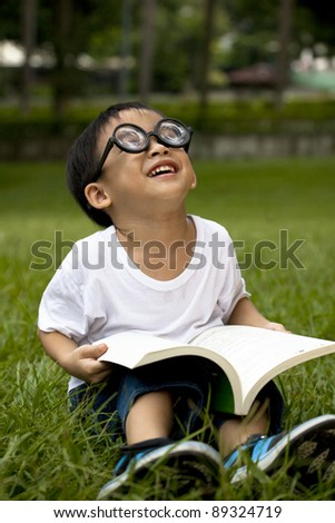 happy asian boy study on the green grass